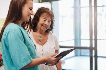 Young nurse and senior woman using digital tablet in nursing home - MASF11189