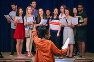 Young female conductor directing choir on stage in auditorium - MASF11231