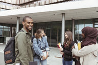 Portrait of smiling man standing with female friends talking at campus in university - MASF11318