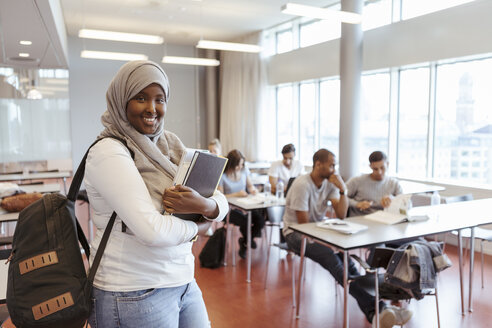 Portrait of smiling student in hijab standing with book against friends in classroom - MASF11321