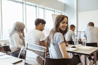 Portrait of smiling student sitting with friends in classroom at high school - MASF11324