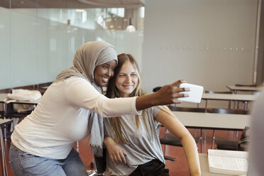 Smiling woman in hijab taking selfie with friend on smart phone at classroom - MASF11327