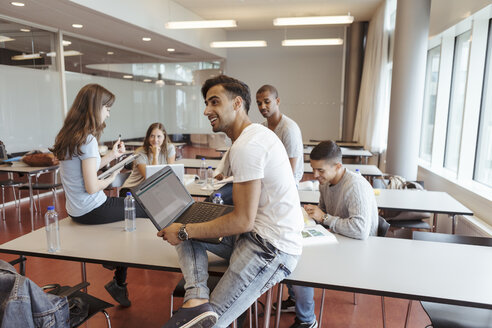 Smiling man using laptop while sitting with friends in university classroom - MASF11330