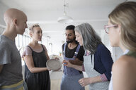 Female instructor showing clay dish to students in pottery class art studio - HEROF22659