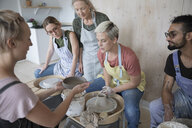 Female instructor showing clay bowl to pottery students at pottery wheels in art studio - HEROF22668