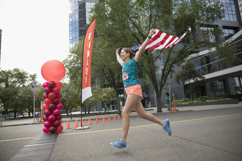 Female marathon runner running with American flag, crossing finish line - HEROF22698