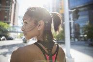 Female runner looking away on sunny urban street - HEROF22701
