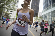 Female marathon runner wearing marathon bib, running on urban street - HEROF22704