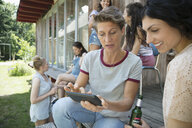Female friends drinking beer and texting with cell phone on cabin patio - HEROF22707