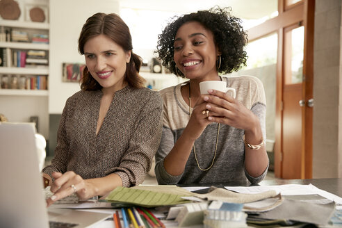 Female interior designers working at laptop at home office desk - HEROF22725