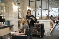 Female hair stylist blow drying hair of customer in hair salon - HEROF22758