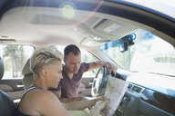 Couple looking at map in car on road trip - HEROF22779