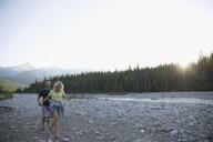 Couple hiking along stream in woods below mountains - HEROF22788