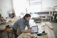 Male carpenter sketching with digital tablet stylus at workbench in workshop - HEROF22827