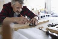 Focused male carpenter measuring and marking wood in workshop - HEROF22833