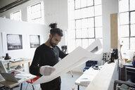 Male photographer examining large photograph print in art studio - HEROF22845