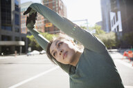 Female runner stretching on sunny urban street - HEROF22851