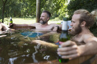 Male friends relaxing and drinking beer, soaking in hot tub - HEROF22872