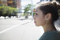 Pensive woman looking away on sunny urban street - HEROF22956