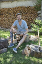 Portrait smiling man drinking beer, chopping wood and texting with cell phone in rural yard - HEROF22965