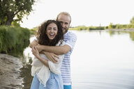 Portrait playful young couple hugging at summer lake - HEROF22974