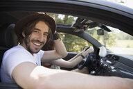 Portrait smiling man with beard riding in car, enjoying road trip - HEROF23058
