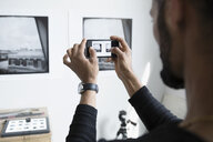 Male photographer with camera phone photographing prints on wall in art studio - HEROF23097