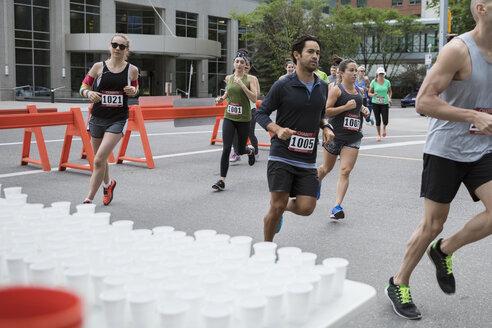 Marathon runners running, turning corner at water station on urban street - HEROF23103
