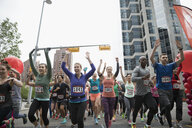 Marathon runners running and cheering with arms raised on urban street - HEROF23115