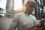 Male runner using smart phone, listening to music with earbud headphones on urban street - HEROF23124