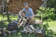 Man drinking beer, chopping wood and texting with cell phone in rural yard - HEROF23127