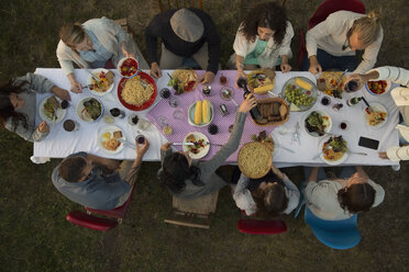 Overhead view friends eating and drinking at garden party dinner - HEROF23133