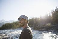 Man with beard wearing sunglasses and hat, hiking along sunny summer stream - HEROF23205