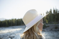 Pensive blonde woman wearing sun hat, looking at view in woods - HEROF23208