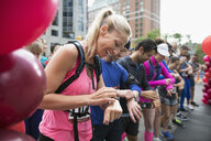 Smiling female marathon runner ready, preparing smart watch at starting line on urban street - HEROF23232