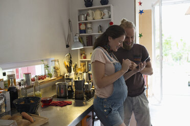 Pregnant couple using cell phone in kitchen - HEROF23265