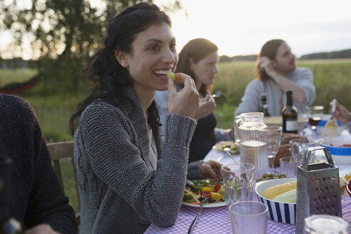 Smiling woman eating and enjoying garden party dinner - HEROF23274