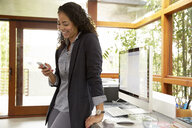 Smiling businesswoman texting with cell phone in office - HEROF23289