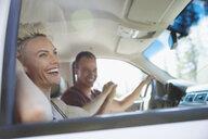 Smiling couple holding hands in car, enjoying trip - HEROF23325