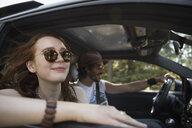 Smiling, carefree woman enjoying breeze, riding in car on road trip - HEROF23340