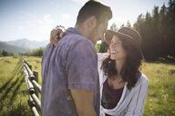 Smiling affectionate young couple hugging and laughing in sunny summer rural grass - HEROF23346