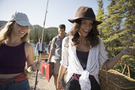 Smiling friends carrying fishing rod, picnic basket and canoes at sunny lakeside - HEROF23349