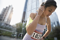 Young female marathon runner resting, listening to music with earbud headphones - HEROF23370