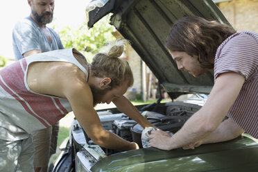 Young male friends fixing car engine - HEROF23388