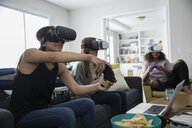Teenage girl friends playing video games with virtual reality simulators in living room - HEROF23412