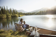 Young couple relaxing in canoe on sunny summer lake - HEROF23463