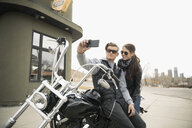 Biker couple with camera phone taking selfie on motorcycle in parking lot - HEROF23478