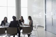 Businesswomen brainstorming, discussing paperwork in conference room meeting - HEROF23508