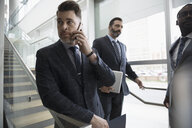 Businessman talking on cell phone on office stairs - HEROF23568