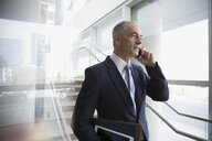 Businessman talking on cell phone on office stairs - HEROF23580